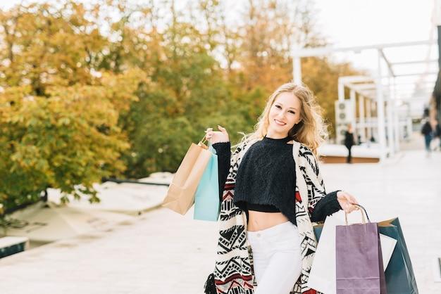 Mulher sorridente, com, coloridos, sacolas, em, outono, parque