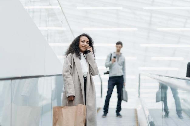 Mulher sorridente com compras em pé na escada rolante do shopping center