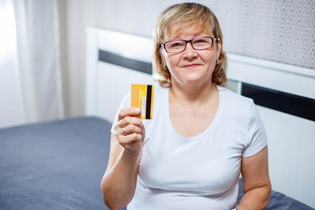Mulher sorridente com computador portátil e cartão de crédito.