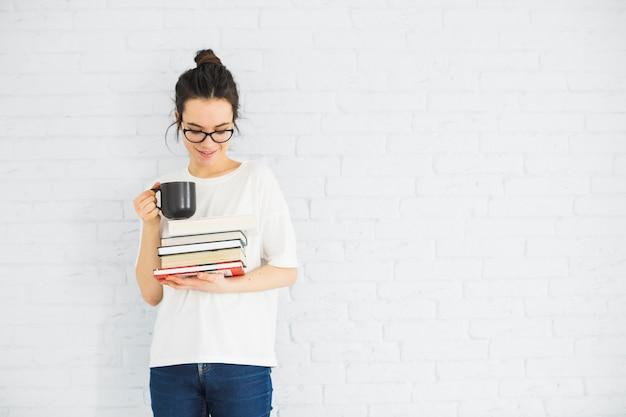 Mulher sorridente, com, copo, e, livros