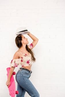 Mulher sorridente, com, cor-de-rosa, skateboard, e, chapéu