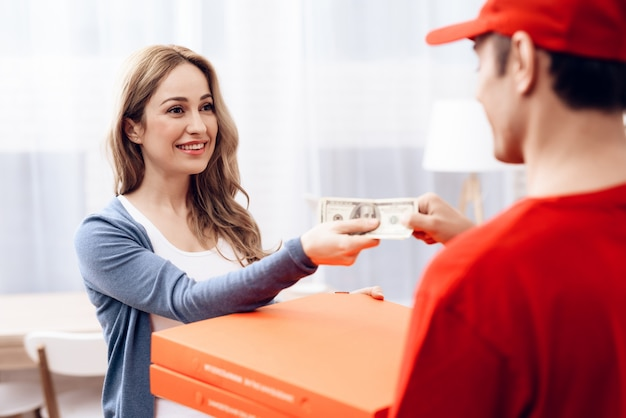 Mulher sorridente com courier pizza delivery payment.