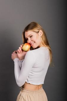 Mulher sorridente com dentes saudáveis segurando uma maçã vermelha, retrato isolado em estúdio, fundo cinza