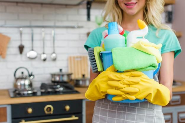 Mulher sorridente com equipamentos de limpeza pronto para limpar a casa