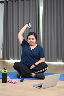 Mulher sorridente com excesso de peso, exercitando-se e assistindo a vídeos de treinamento de fitness online no laptop em casa.