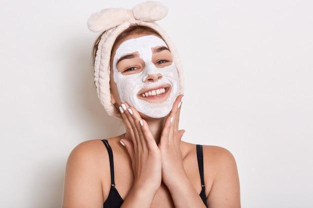 Mulher sorridente com faixa na cabeça aplicada máscara na pele do rosto, olhando sorrindo diretamente para a câmera, mantendo a palma da mão em suas bochechas, posando isolado sobre fundo branco.