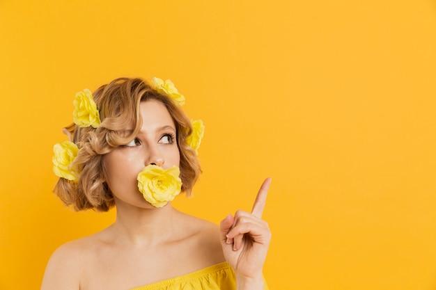 Mulher sorridente com flores amarelas apontando