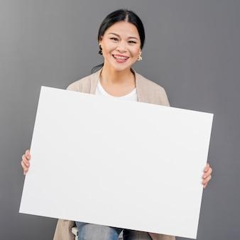 Mulher sorridente com folha de papel em branco