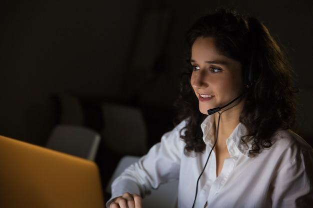 Mulher sorridente com fone de ouvido no escritório escuro
