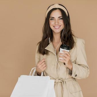 Mulher sorridente com fones de ouvido e sacolas de compras