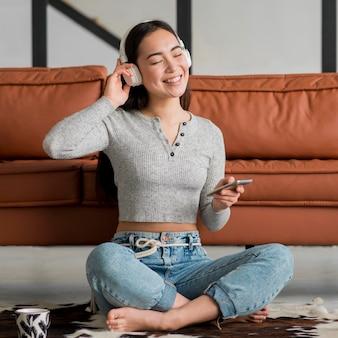 Mulher sorridente com fones de ouvido, ouvindo música