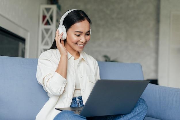 Mulher sorridente com fones de ouvido trabalhando em um laptop