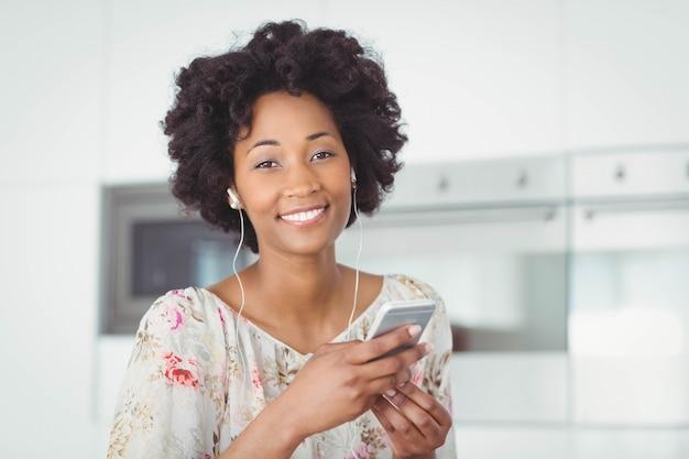 Mulher sorridente, com, fones ouvido, usando, smartphone, cozinha