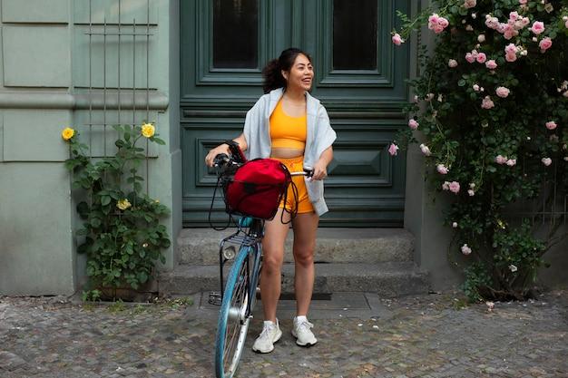 Mulher sorridente com foto completa com bicicleta