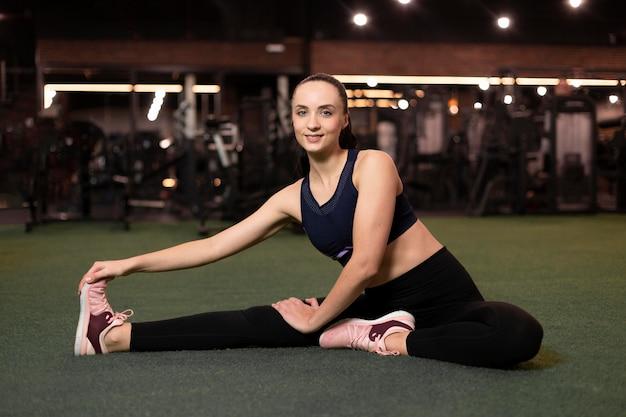 Mulher sorridente com foto completa esticando a perna