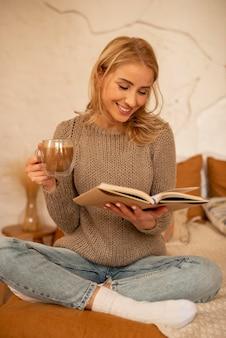 Mulher sorridente com foto completa lendo