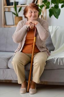 Mulher sorridente com foto completa sentada no sofá