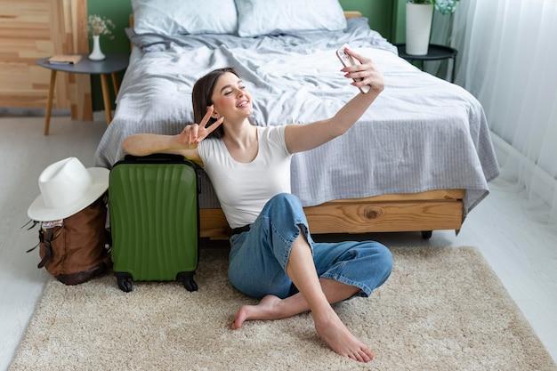 Mulher sorridente com foto completa tirando selfie