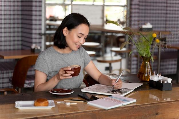 Mulher sorridente com foto média desenhando