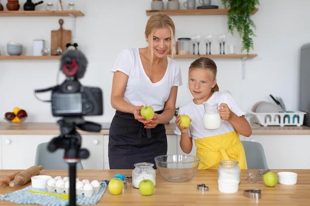 Mulher sorridente com foto média e garota gravando