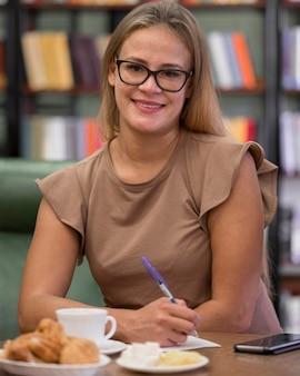 Mulher sorridente com foto média na biblioteca