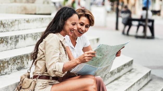 Mulher sorridente com foto média olhando para o mapa