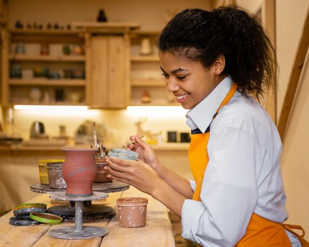 Mulher sorridente com foto média pintando panela de barro