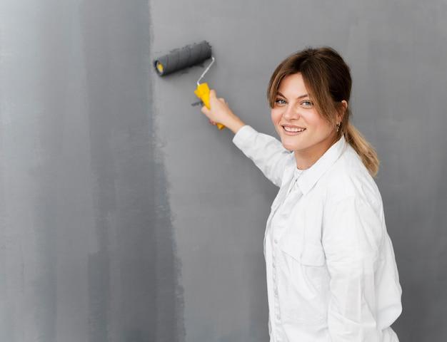 Mulher sorridente com foto média pintando parede