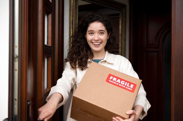 Mulher sorridente com foto média segurando caixa