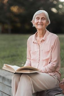 Mulher sorridente com foto média segurando livro