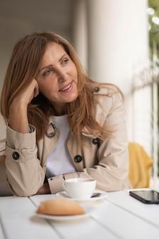 Mulher sorridente com foto média sentada à mesa