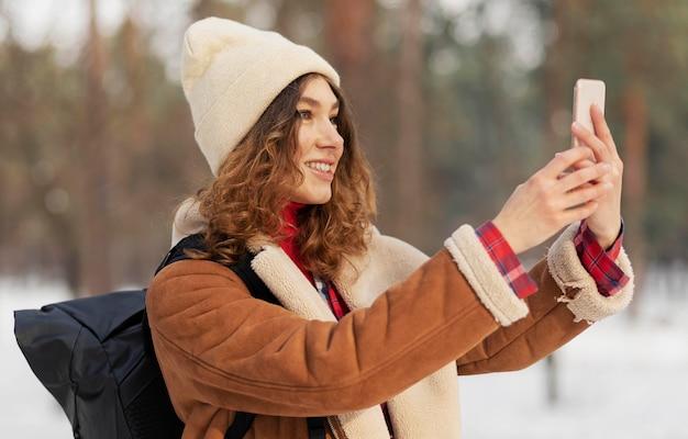 Mulher sorridente com foto média tirando selfies