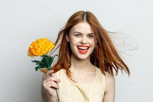 Mulher sorridente com grande flor amarela em alegria de emoções de mãos. foto de alta qualidade