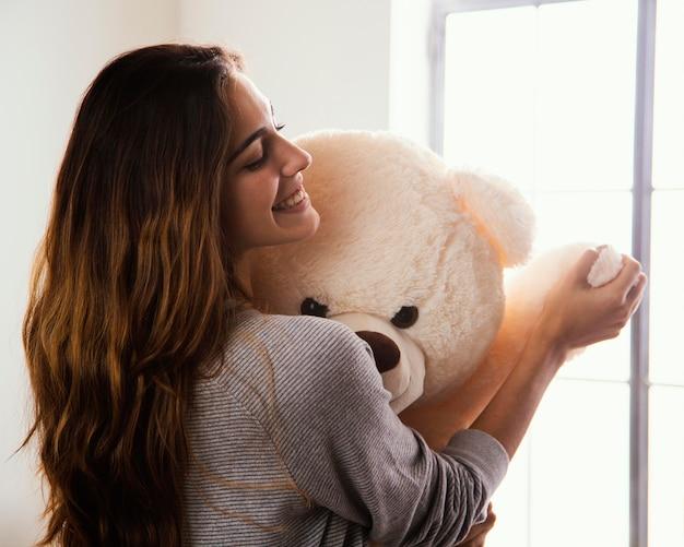 Mulher sorridente com grande ursinho de pelúcia em casa