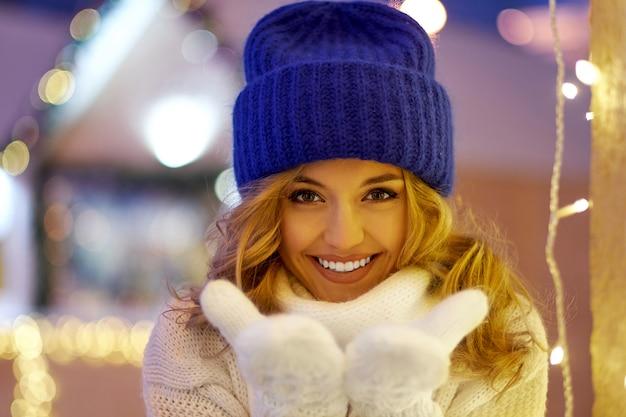 Mulher sorridente com guirlandas e luzes do feriado