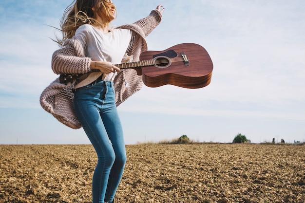 Mulher sorridente com guitarra pulando no campo