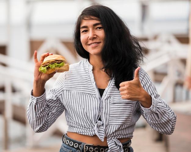Mulher sorridente com hambúrguer mostrando aprovação