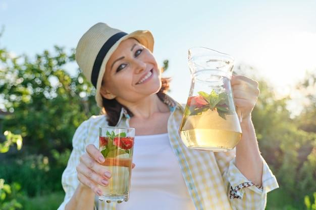 Mulher sorridente com jarra de bebida caseira natural refrescante