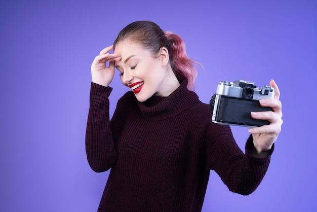 Mulher sorridente com lábios vermelhos tenta tirar selfie com uma câmera