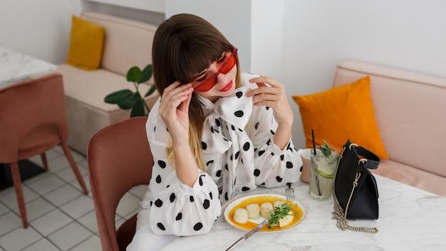 Mulher sorridente com lábios vermelhos, tomando café da manhã
