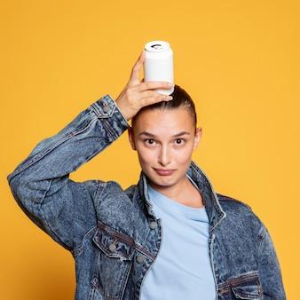 Mulher sorridente com lata de refrigerante na cabeça