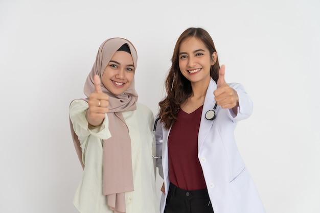 Mulher sorridente com lenço na cabeça e feliz linda médica com polegares para cima gesto de pé ao lado. Foto Premium
