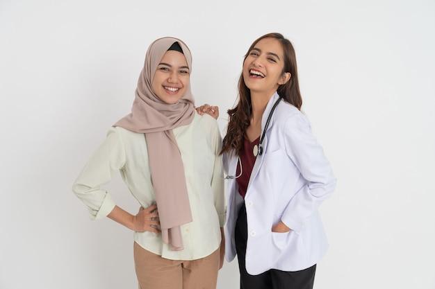 Mulher sorridente com lenço na cabeça e linda médica feliz olhando para a câmera em pé de lado.