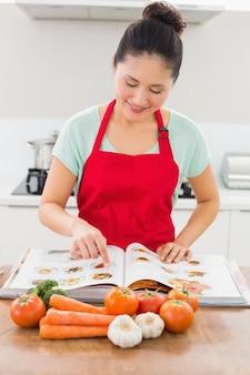 Mulher sorridente com livro de receitas e vegetais na cozinha