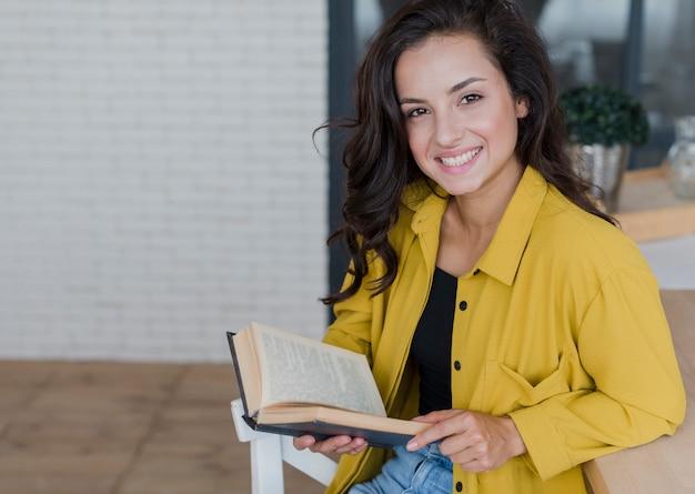 Mulher sorridente com livro, olhando para a câmera