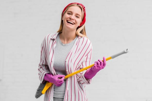 Mulher sorridente com luvas cantando na escova