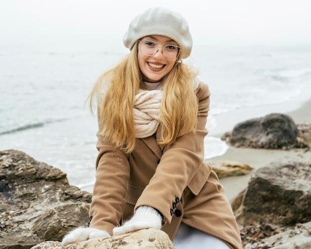 Mulher sorridente com luvas na praia durante o inverno