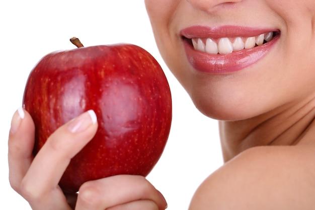 Mulher sorridente com maçã isolada no branco