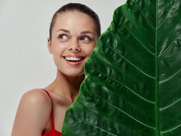 Mulher sorridente com maiô vermelho, vista lateral em folha de palmeira, close-up