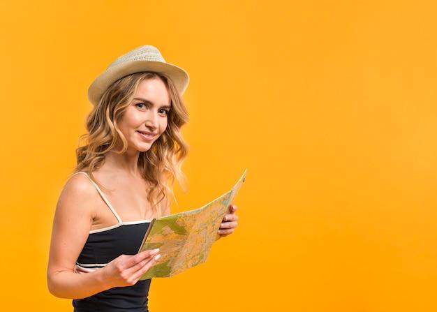 Mulher sorridente, com, mapa, em, verão, equipamento